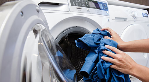 Person putting shirt into front loading washing machine
